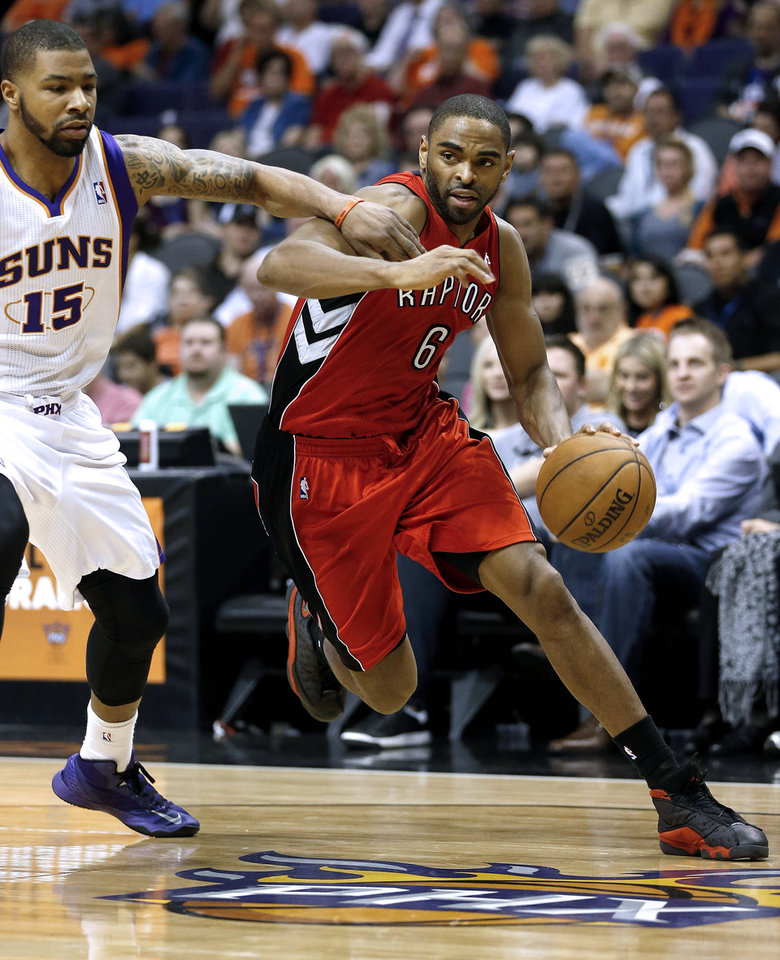 Photo - Toronto Raptors' Alan Anderson (6) drives against Phoenix Suns' Marcus Morris (15) during the first half of an NBA basketball game, Wednesday, March 6, 2013, in Phoenix.  (AP Photo/Matt York)