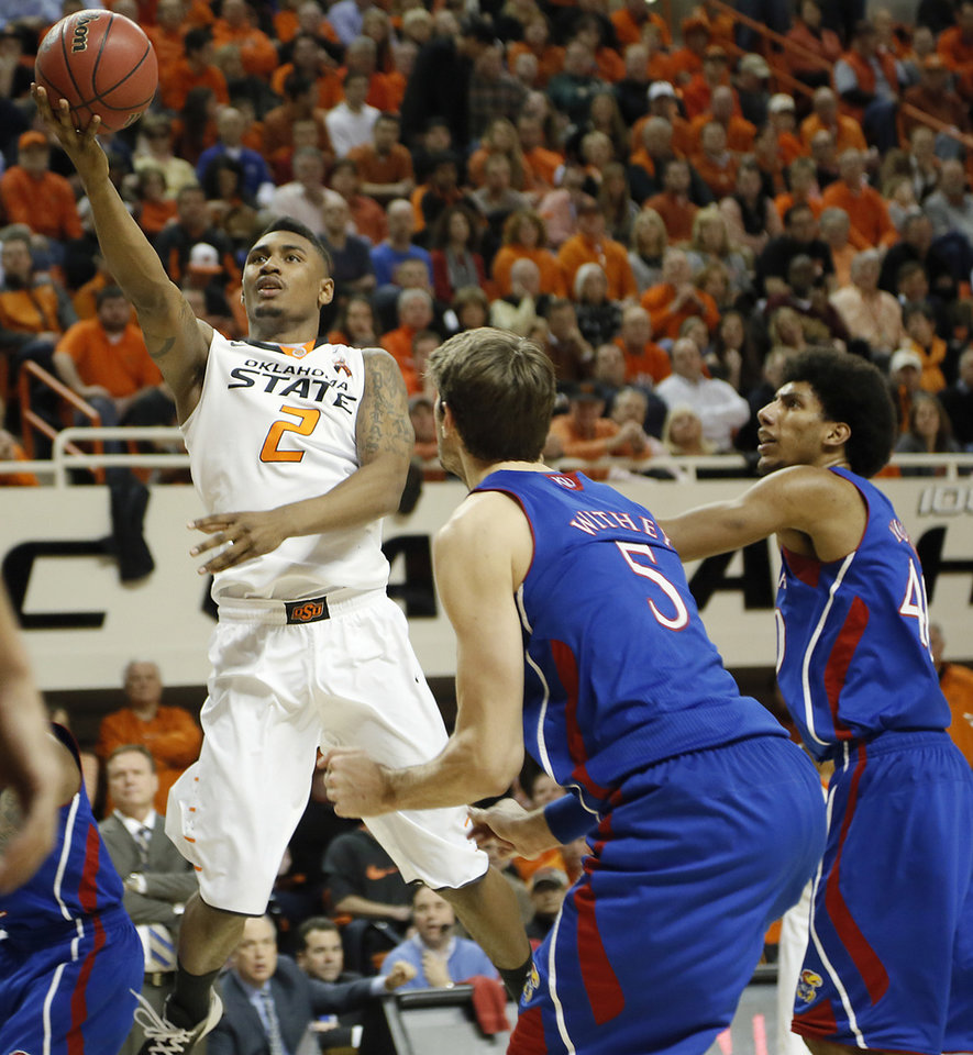 Photo - Oklahoma State 's Le'Bryan Nash (2) drives past Kansas' Jeff Withey (5) and Kevin Young (40) during the college basketball game between the Oklahoma State University Cowboys (OSU) and the University of Kanas Jayhawks (KU) at Gallagher-Iba Arena on Wednesday, Feb. 20, 2013, in Stillwater, Okla. Photo by Chris Landsberger, The Oklahoman