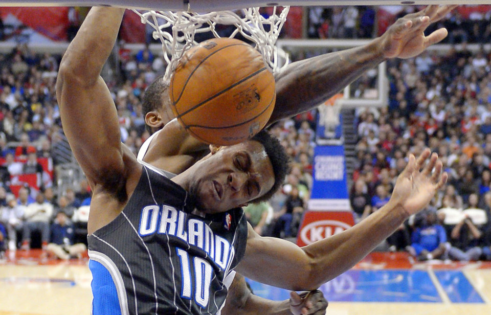Photo - Orlando Magic guard Ish Smith, right, is folded as he dunks by Los Angeles Clippers guard Jamal Crawford during the first half of their NBA basketball game, Saturday, Jan. 12, 2013, in Los Angeles. (AP Photo/Mark J. Terrill)