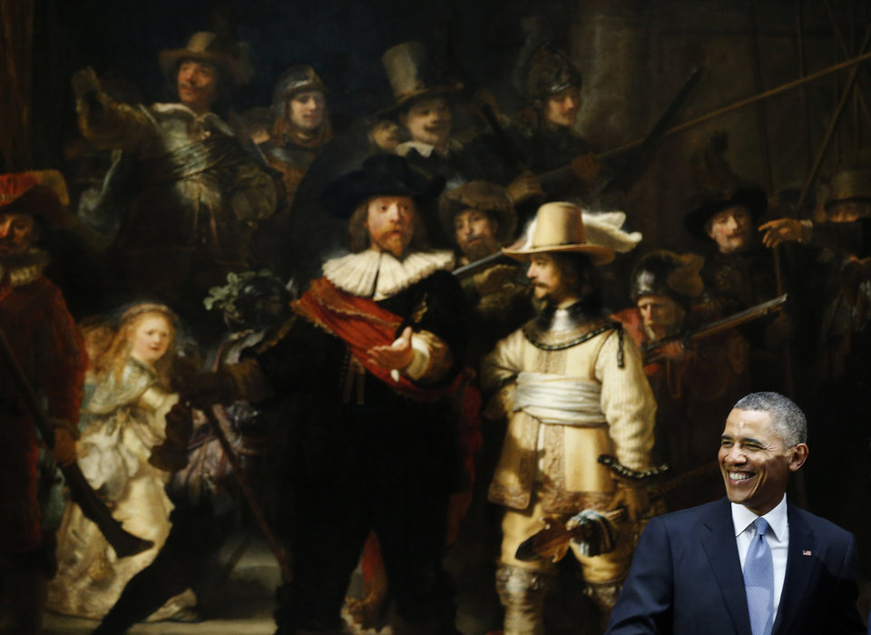 Photo - U.S. President Barack Obama smiles in front of  Dutch master Rembrandt's The Night Watch painting during a visit to the Rijksmuseum in Amsterdam, Netherlands, Monday, March 24, 2014. Obama will attend the two-day Nuclear Security Summit in The Hague. (AP Photo/Frank Augstein)