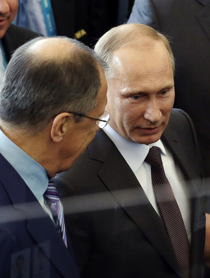 Photo - Russia's President Vladimir Putin talks to Russian Foreign Minister Sergei Lavrov during the World Cup final soccer match between Germany and Argentina at the Maracana Stadium in Rio de Janeiro, Brazil, Sunday, July 13, 2014. (AP Photo/Hassan Ammar)