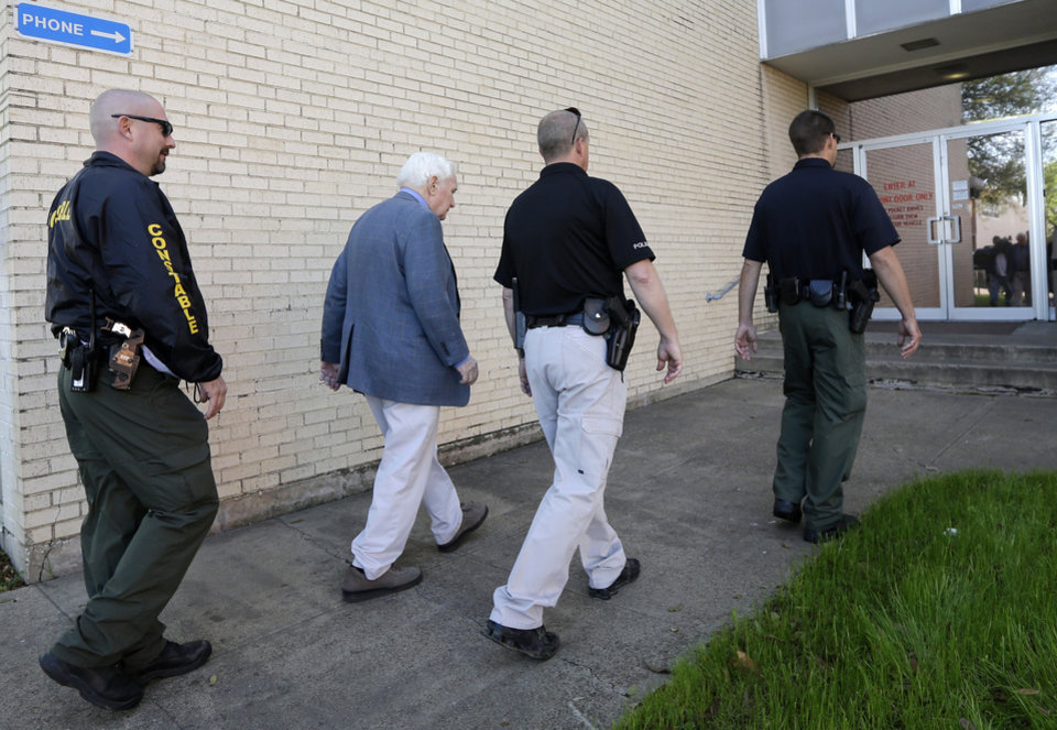 Photo - Kaufman county law enforcement officials escort an employee inside the county courthouse Monday, April 1, 2013, in Kaufman, Texas.   Law enforcement officials throughout Texas remained on high alert Monday seeking to better protect prosecutors and their staffs following the killing of county district attorney whose assistant was gunned down just months ago. (AP Photo/Tony Gutierrez)(AP Photo/Tony Gutierrez)
