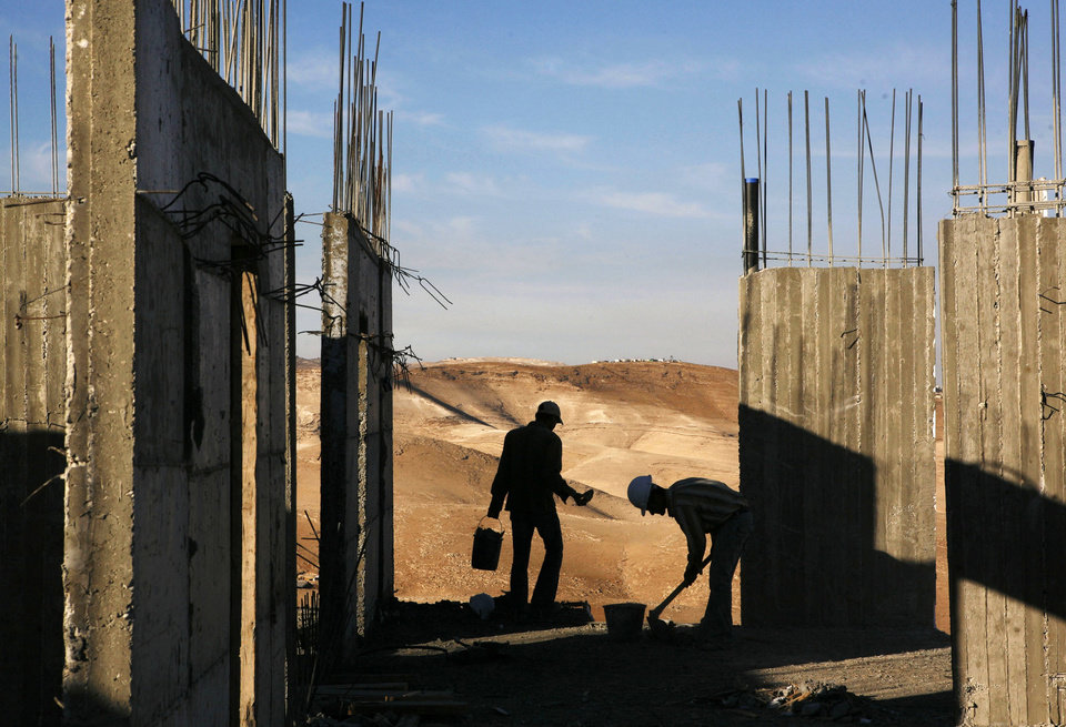 Photo - FILE - In this Wednesday, Nov. 14, 2007 file photo, Palestinian construction laborers work on a new housing development in the West Bank Jewish settlement of Maaleh Adumim, near Jerusalem. Israel on Wednesday, Oct. 30, 2013, announced plans to build 1,500 new homes in east Jerusalem, the part of the city claimed by the Palestinians, just hours after it freed a group of Palestinian prisoners as part of a deal to set peace talks in motion. (AP Photo/Kevin Frayer, File)