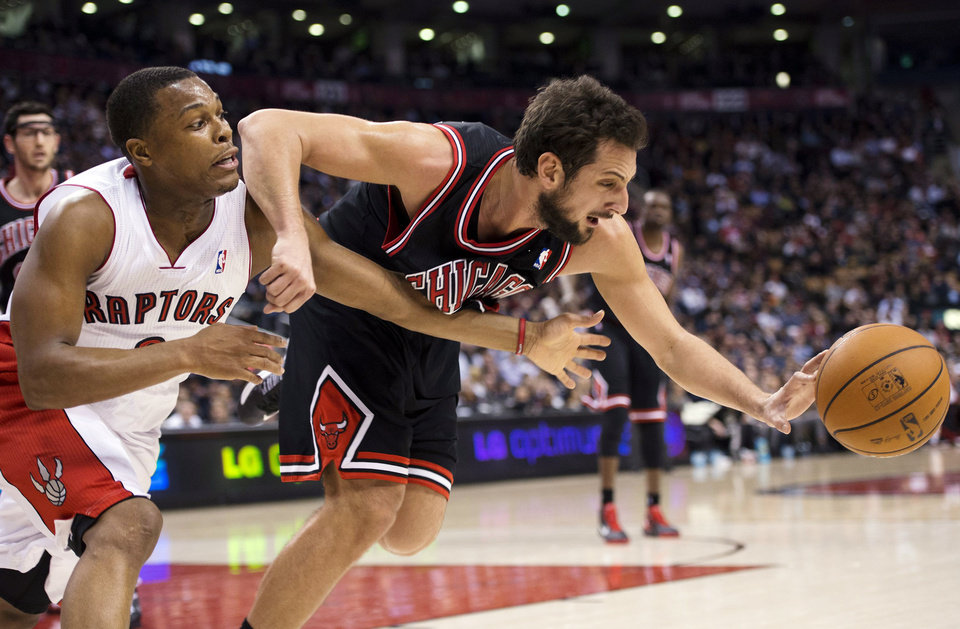 Toronto Raptors guard Kyle Lowry, left, battles for the ball against Chicago Bulls guard Marco Belinelli during the first half of their NBA basketball game, Wednesday, Jan. 16, 2013, in Toronto. (AP Photo/The Canadian Press, Nathan Denette)