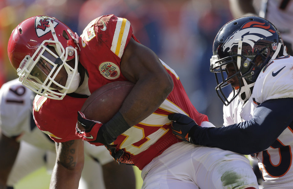Photo -   Kansas City Chiefs running back Shaun Draughn (20) is tackled by Denver Broncos strong safety Mike Adams, right, during the first half of an NFL football game at Arrowhead Stadium in Kansas City, Mo., Sunday, Nov. 25, 2012. (AP Photo/Charlie Riedel)