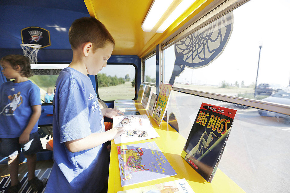 Photo - Michael Allman, 9, looks at books during the Thunder Book Bus visit to  Mustang Christian Academy in Mustang, Thursday, September 12, 2013. Photo By Steve Gooch, The Oklahoman