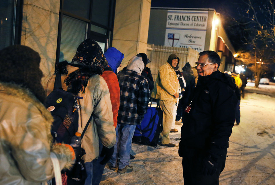 Before dawn and in -9 degree weather, Tom Tuning, right, greets men who wait for the opening of the St. Francis Center's day shelter, where Tuning is finance director, in downtown Denver, Thursday Dec. 5, 2013. A wintry storm pushing through the western half of the country has brought bitterly cold temperatures that prompted safety warnings for residents in the Rockies and threatened crops as far south as California. (AP Photo/Brennan Linsley)