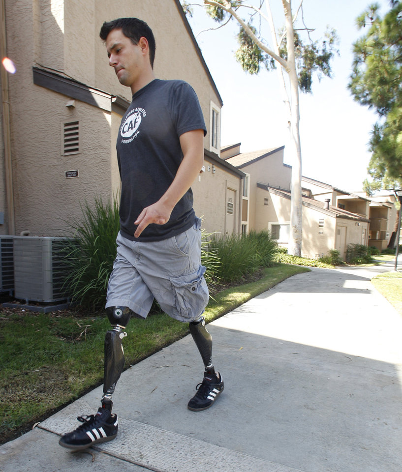 "In this Thursday, Oct. 4, 2012 photo, former U.S. Marine Cpl. Daniel Riley, 21, walks with prosthetic legs outside his apartment in San Diego. Riley lost both legs to an IED in Afhganistan. Learning to walk on his prosthetic legs was ""like kicking a soccer ball in a swimming pool."" But he didn't just learn to walk; he has learned to soar. He joined ""Operation Rebound,"" and has graduated from competitor to mentor. (AP Photo/Lenny Ignelzi)"