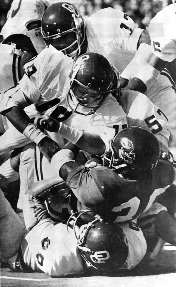 """Photo -  """"SOONER SANDWICH---Kansas running back Laverne Smith, dark jersey, is sandwiched between Oklahoma's Duane Baccus, bottom, Zac Henderson (19), Obie Moore (57) and Jerry Anderson (17), who are on top of Smith during Saturday's game at Lawrence.  Oklahoma beat Kansas 28-10.    Staff photo via AP taken 10/16/76; photo ran in the 10/18/76 Oklahoma City Times. File:  Football/OU/OU-Kansas/Zac Henderson/1976"""