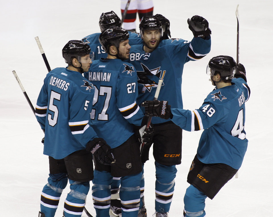 Photo - San Jose Sharks' Scott Hanaan (27) celebrates with teammates, from left, Jason Demers, Joe Thornton, Brent Burns and Tomas Hertl (48) after scoring a goal against the New Jersey Devils during the first period of an NHL hockey game on Saturday, Nov. 23, 2013, in San Jose, Calif. (AP Photo/George Nikitin)