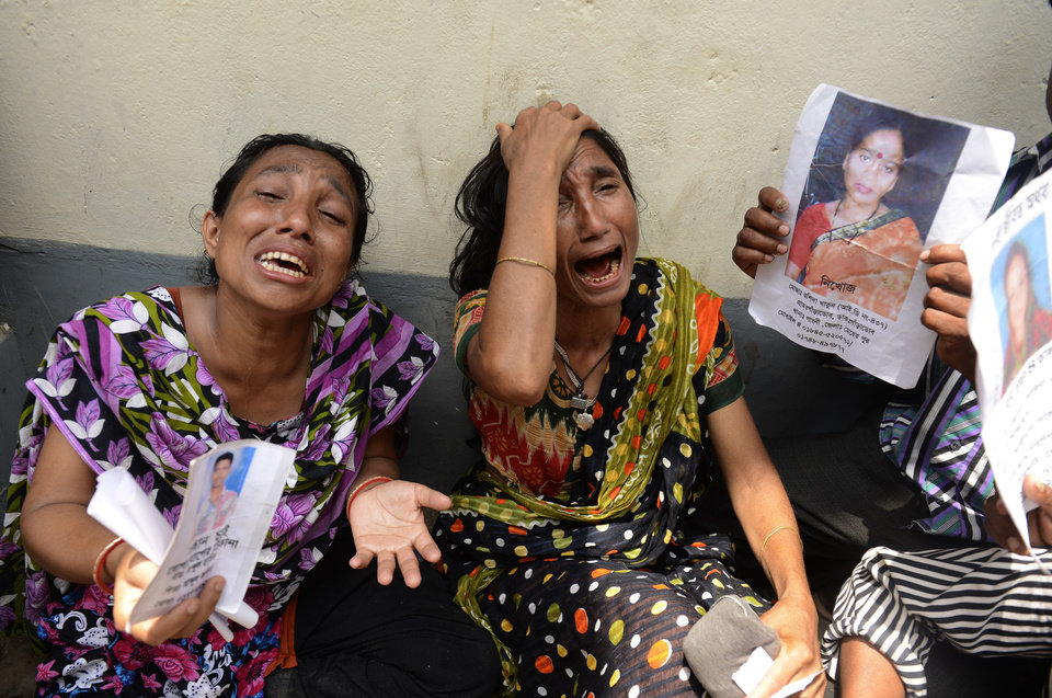 Photo - Relatives of victims from the garment factory building collapse grieve at a morgue on Wednesday May 1, 2013 in Dhaka, Bangladesh where a building housing garment factories that collapsed last week in the country's worst industrial disaster, left at least 402 people dead and injured 2,500. (AP Photo/Ismail Ferdous)