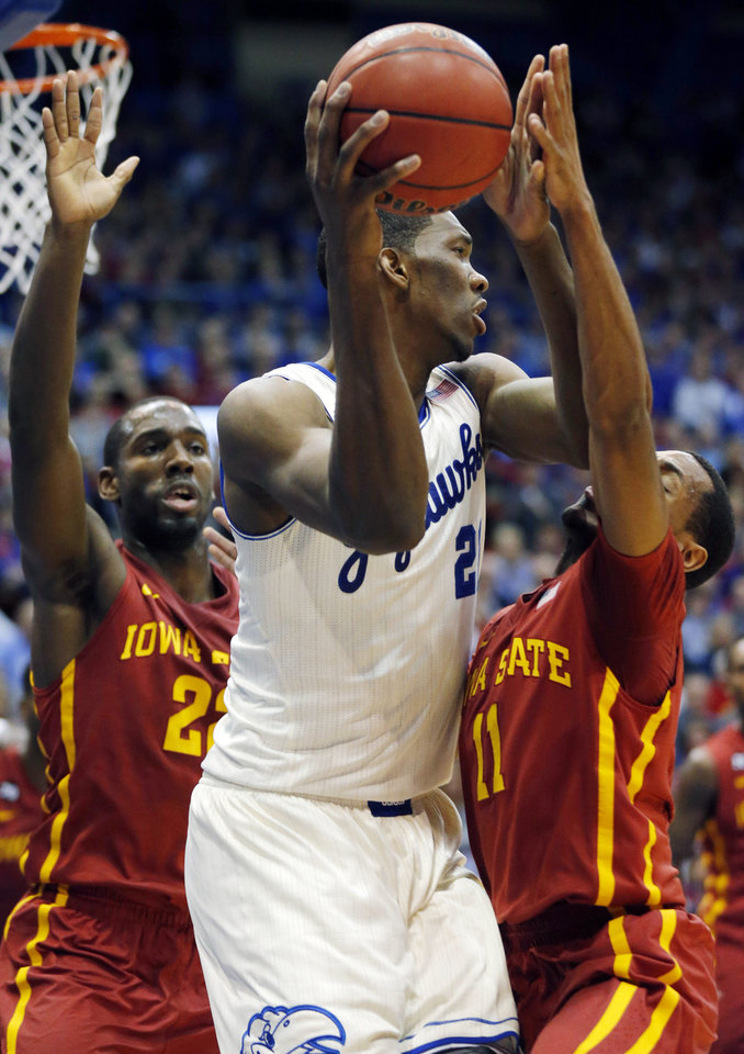Photo - Kansas center Joel Embiid, center, works between Iowa State defenders Dustin Hogue, left, and Monte Morris (11) during the first half of an NCAA college basketball game in Lawrence, Kan., Wednesday, Jan. 29, 2014. (AP Photo/Orlin Wagner)