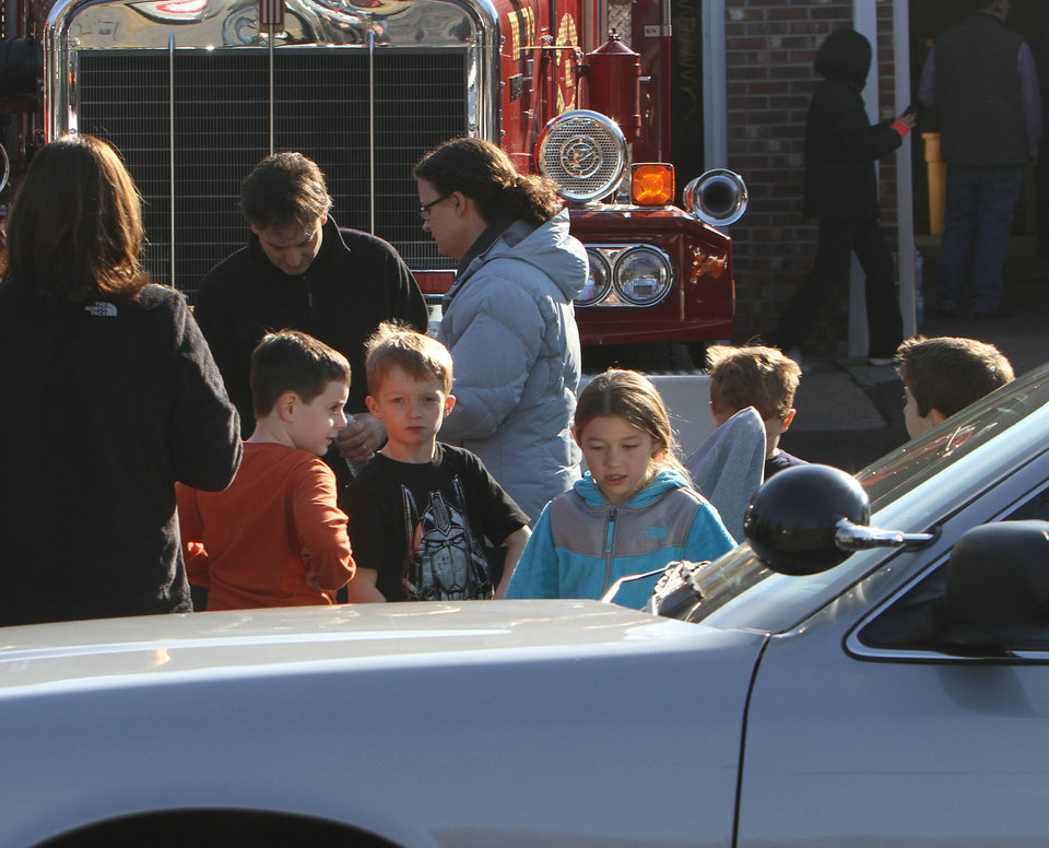 Photo - School children wait for their parents at the Sandy Hook firehouse following a mass shooting at the Sandy Hook Elementary School in Newtown, Conn. where authorities say a gunman opened fire, leaving 27 people dead, including 20 children, Friday, Dec. 14, 2012. (AP Photo/The Journal News, Frank Becerra Jr.) MANDATORY CREDIT, NYC OUT, NO SALES, TV OUT, NEWSDAY OUT; MAGS OUT ORG XMIT: NYWHI105