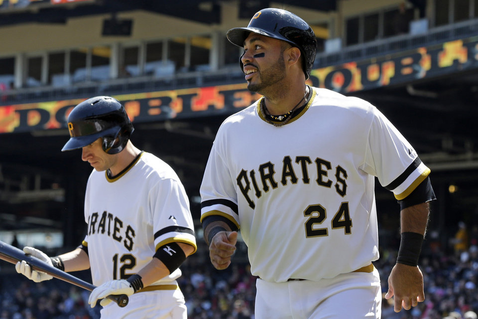 Pittsburgh Pirates\' Pedro Alvarez (24) heads back to the dugout after scoring on a double by teammate Russell Martin (not shown) during the second inning of a baseball game against the Atlanta Braves in Pittsburgh, Sunday, April 21, 2013. Pirates\' Clint Barmes (12) looks on. (AP Photo/Gene J. Puskar)