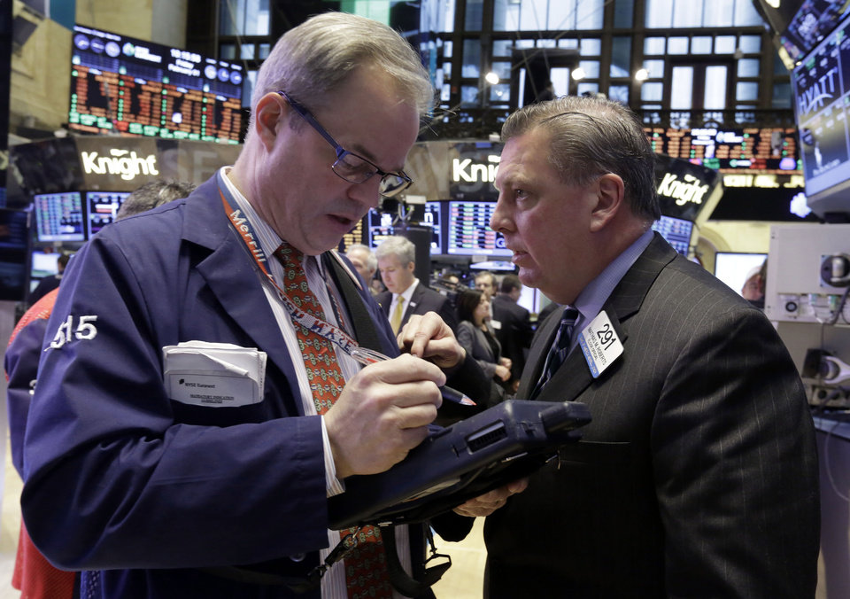 Photo - Traders David O'Day, left, and Mathias Roberts work on the floor of the New York Stock Exchange, Friday, Feb. 1, 2013. The Dow Jones industrial average briefly topped 14,000 on Friday morning, a milestone not seen since before the financial crisis rocked the markets and the world economy. Evidence that the U.S. economic recovery is firmly on track drove markets higher on Friday, adding to the cheer from good economic indicators out of Europe. (AP Photo/Richard Drew)