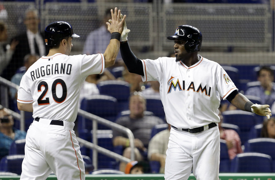 Miami Marlins' Justin Ruggiano (20) and Marcell Ozuna, right, high-five after scoring on a single by Nick Green in the eighth inning during a baseball game against the Philadelphia Phillies in Miami, Monday, May 20, 2013. The Marlins defeated the Phillies 5-1. (AP Photo/Lynne Sladky)