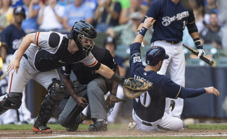 Photo - Milwaukee Brewers' Jonathan Lucroy slides safely past the tag of San Francisco Giants' Andrew Susac during the first inning of a baseball game Thursday, Aug. 7, 2014, in Milwaukee. (AP Photo/Tom Lynn)
