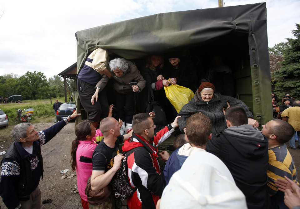 Photo - People help old women out of a military truck during evacuation from Obrenovac, some 30 kilometers (18 miles) southwest of Belgrade Serbia, Saturday, May 17, 2014. Record flooding in the Balkans leaves at least 20 people dead in Serbia and Bosnia and is forcing tens of thousands to flee their homes. Meteorologists say the flooding is the worst since records began 120 years ago. (AP Photo/Darko Vojinovic)