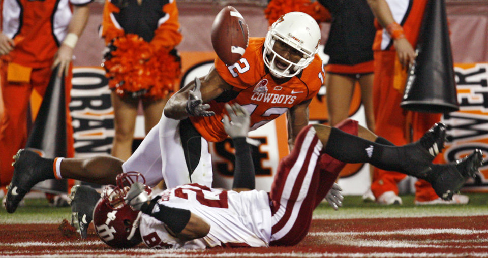 Photo - Oklahoma State's Adarius Bowman (12) has a touchdown pass broken up by Indiana's Leslie Majors (28) during second half of the Insight Bowl college football game between Oklahoma State University (OSU) and the Indiana University Hoosiers (IU) at Sun Devil Stadium on Monday, Dec. 31, 2007, in Tempe, Ariz. 