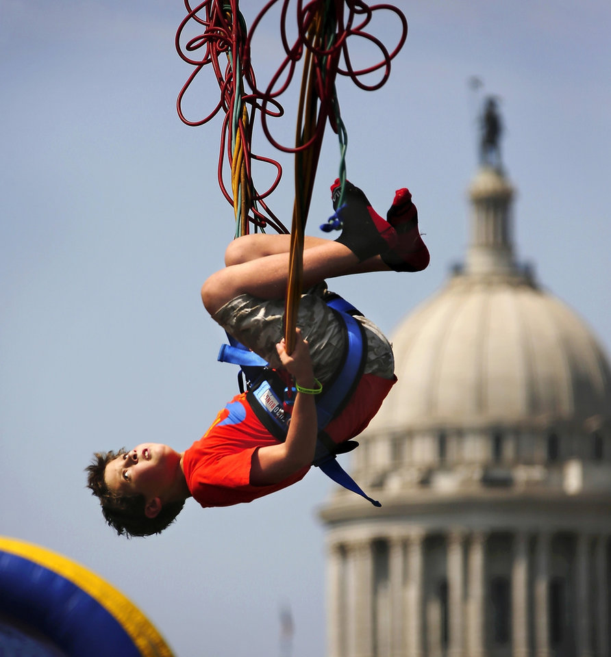 Max Wolfley, 11, of Oklahoma City, flips himself while playing on a bungee/trampoline exhibit. Children and adults crowded the lawns surrounding the Governor's Mansion on Saturday, Sep. 7, 2013, to enjoy a variety of activities aimed at young Oklahomans during the 17th Annual Septemberfest. Admission was free. Photo  by Jim Beckel, The Oklahoman.