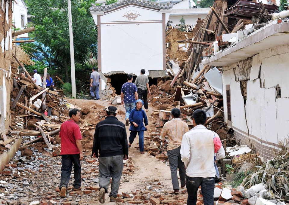 Photo - People walk by collapsed houses  after Sunday's earthquake in Ludian County of Zhaotong City in southwest China's Yunnan Province, Monday, Aug. 4, 2014. Rescuers dug through shattered homes Monday looking for survivors of a strong earthquake in southern China's Yunnan province that killed hundreds and injured more than a thousand people. (AP Photo/Kyodo News) JAPAN OUT