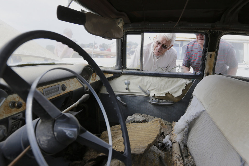 Photo - Car buffs look at a 1956 Chevrolet Belair 4 door Sedan during a preview for an auction of vintage cars and trucks from the former Lambrecht Chevrolet dealership in Pierce, Neb., Friday Sept. 27, 2013. The auction takes place on Saturday and Sunday. (AP Photo/Nati Harnik)