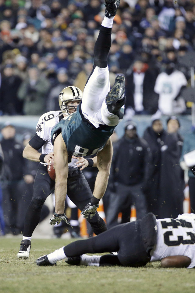 Photo - New Orleans Saints' Drew Brees, left, tries to pass as Philadelphia Eagles' Connor Barwin, center, is upended by Darren Sproles during the second half of an NFL wild-card playoff football game, Saturday, Jan. 4, 2014, in Philadelphia. (AP Photo/Matt Rourke)