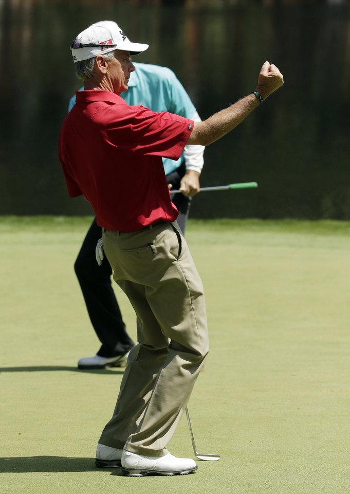 Photo - Larry Mize pumps his fist after a birdie on the ninth hole during the par three competition at the Masters golf tournament Wednesday, April 9, 2014, in Augusta, Ga. (AP Photo/Chris Carlson)