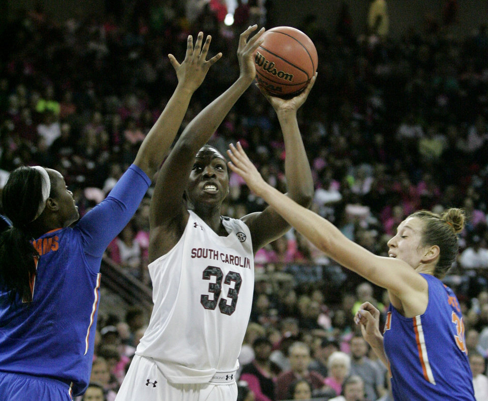 Photo - South Carolina's Elam Ibiam (33) takes attempts a shot as Florida's Jaterra Bonds and Lily Svete, right, defend during the first half of their NCAA women's college basketball game, Sunday, Feb. 23, 2014, in Columbia, S.C. (AP Photo/Mary Ann Chastain)