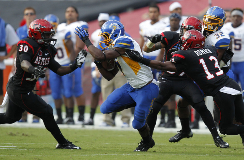 Photo -   San Jose State's Tyler Ervin, center, breaks tackles for a 97-yard touchdown on a kickoff return during an NCAA college football game against San Diego State, Saturday , Sept. 22, 2012, in San Diego. (AP Photo/UT San Diego, Earnie Grafton) SAN DIEGO COUNTY OUT; NO SALES; COMMERCIAL INTERNET OUT; FOREIGN OUT