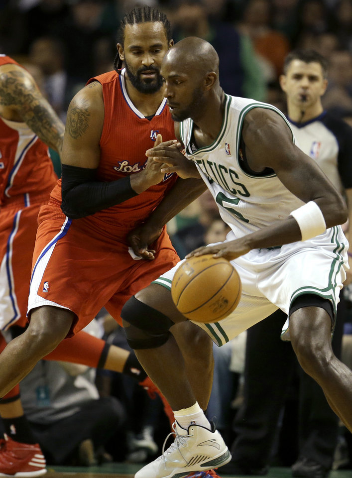 Photo - Boston Celtics forward Kevin Garnett (5), right, tries to drive toward the basket past Los Angeles Clippers center Ronny Turiaf , left, of France, in the second quarter of an NBA basketball game in Boston, Sunday, Feb. 3, 2013. The Celtics defeated the Clippers 106-104. (AP Photo/Steven Senne)