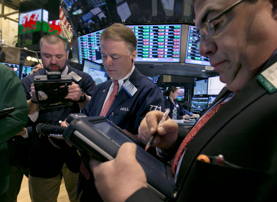 Photo - Traders work on the floor of the New York Stock Exchange, Friday, Feb. 28, 2014. U.S. stocks are opening higher, pushing the market further into record territory. (AP Photo/Richard Drew)
