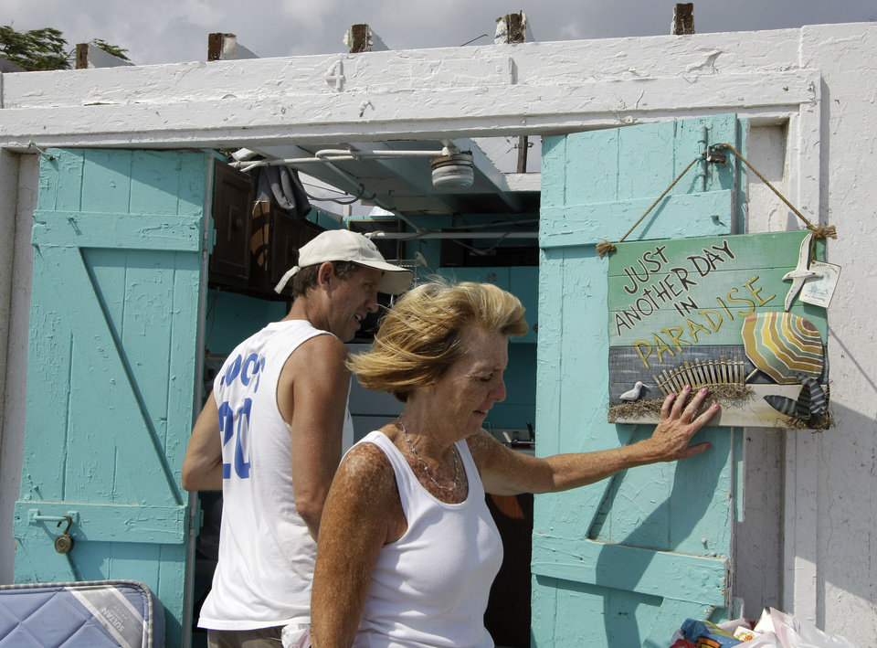 Photo -   Bill Ryan watches as his wife Janet hangs up a picture in front of their roofless cabana at the Breezy Point Surf Club in the Queens section of New York, Saturday, Sept. 8, 2012, after severe weather passed the area. A tornado swept out of the sea and hit the beachfront neighborhood in New York City, hurling debris in the air, knocking out power and startling residents who once thought of twisters as a Midwestern phenomenon. Firefighters were still assessing the damage, but no serious injuries were reported and the area affected by the storm appeared small. (AP Photo/Kathy Willens)