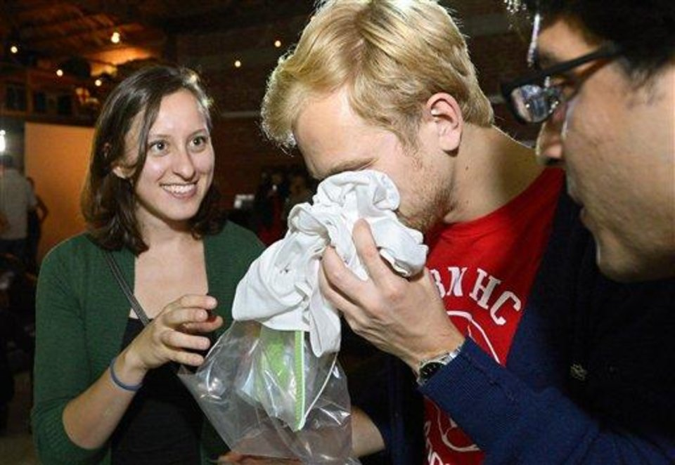 Photo - Konstantin Bakhurin, center, smells a shirt as Martina Desalvo, left, and Neelroop Parikfhak look on during a pheromone party, Friday, June 15, 2012, in Los Angeles. The get-togethers, which have been held in New York and Los Angeles and are planned for other cities, require guests to submit a slept-in T-shirt that will be sniffed by other participants. Then you can pick your partner based on scent. (AP Photo/Mark J. Terrill)