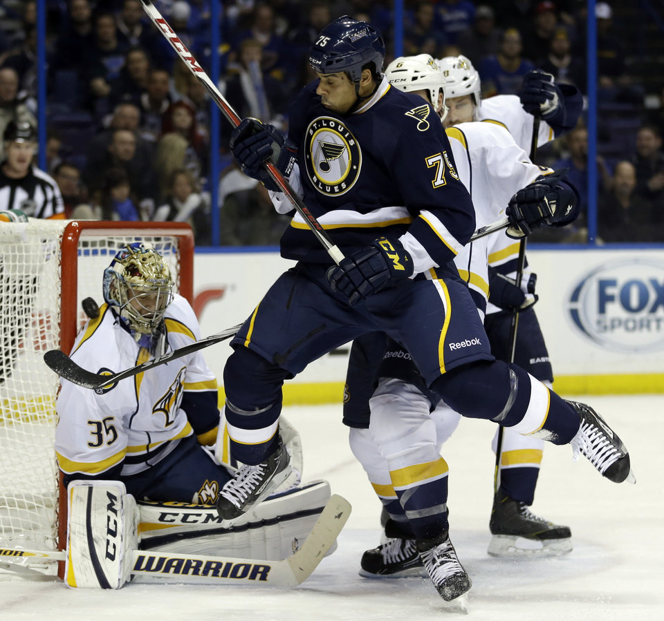 St. Louis Blues\' Ryan Reaves, right, leaps out of the way as he tries to avoid a shot deflected by Nashville Predators goalie Pekka Rinne, of Finland, during the second period of an NHL hockey game on Thursday, Jan. 24, 2013, in St. Louis. (AP Photo/Jeff Roberson)