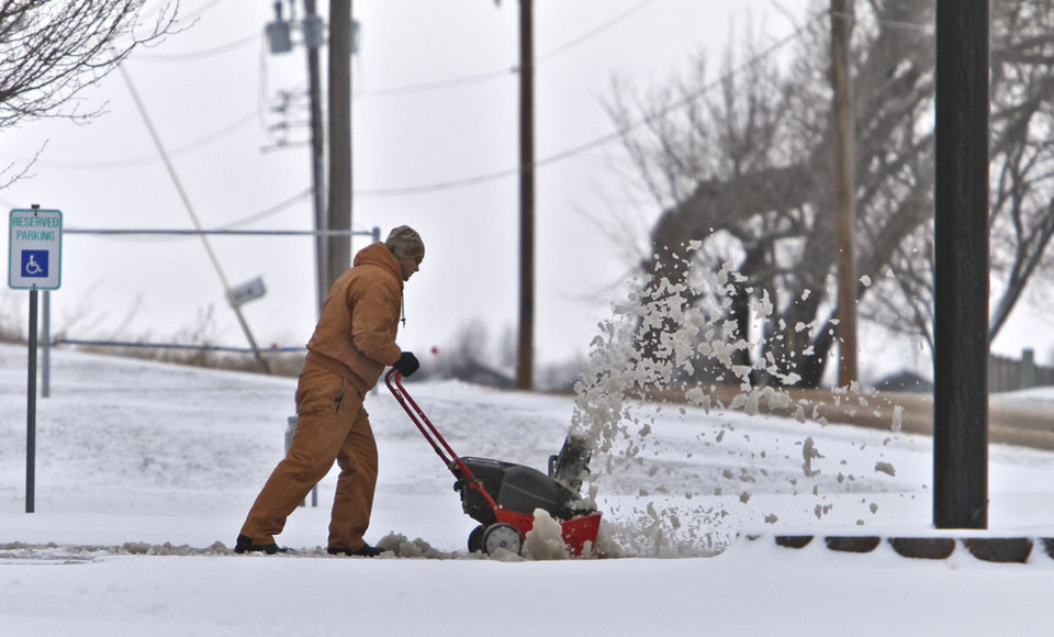 Photo - A business owner uses a snow blower to clear the drive after snow hit the metro area on Monday, Feb. 13, 2012, in Yukon, Okla. Photo by Chris Landsberger, The Oklahoman