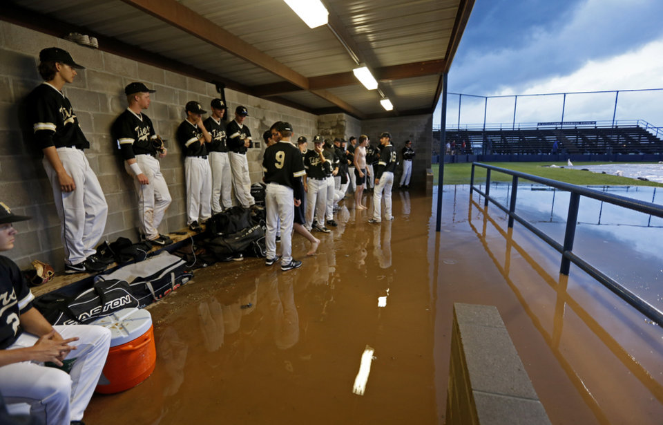 Broken Arrow players wait in a flooded dugout during a weather delay before a Class 6A state baseball tournament game between Broken Arrow and Edmond North in Shawnee, Okla., Thursday, May 9, 2013. Photo by Bryan Terry, The Oklahoman