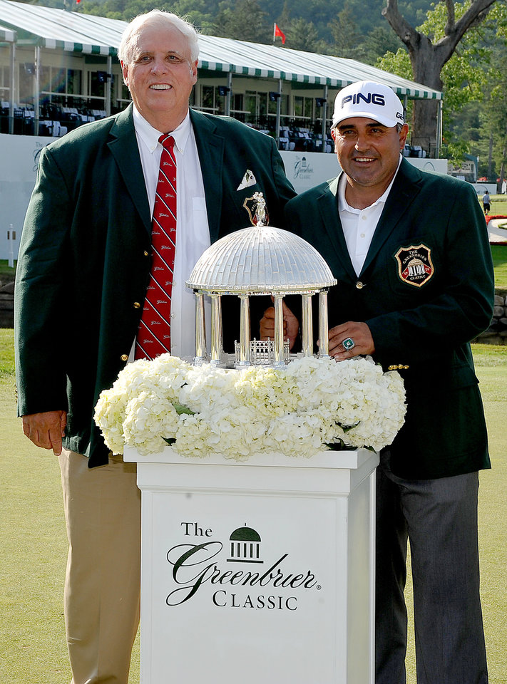 Photo - The Greenbrier's owner Jim Justice, left and winner of the 2014 Greenbrier Classic Angel Cabrera with The Greenbrier Classic Springhouse Trophy  at the conclusion of the Greenbrier Classic golf tournament at the Greenbrier Resort in White Sulphur Springs, W.Va., Sunday, July 6, 2014.  (AP Photo/Chris Tilley)