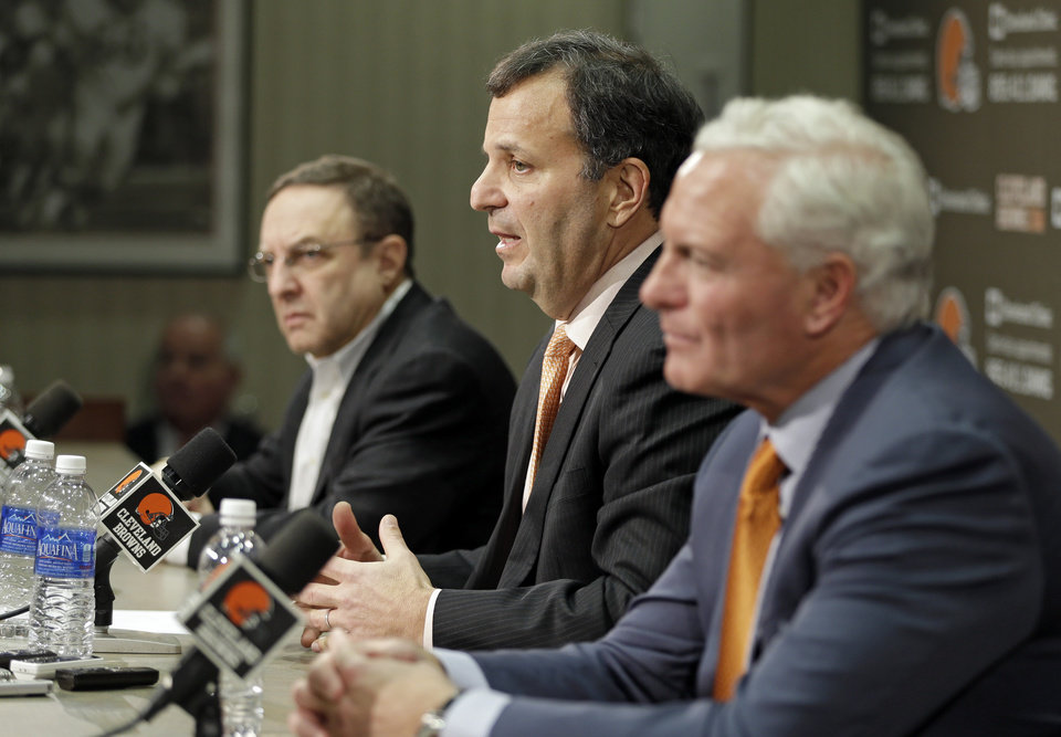 Mike Lombardi, center, the Cleveland Browns' vice president of player personnel, answers questions during his introductory news conference at the NFL football team's practice facility in Berea, Ohio Friday, Jan. 18, 2013. Browns CEO Joe Banner, left, and owner Jimmy Haslam, right, listen. (AP Photo/Mark Duncan)