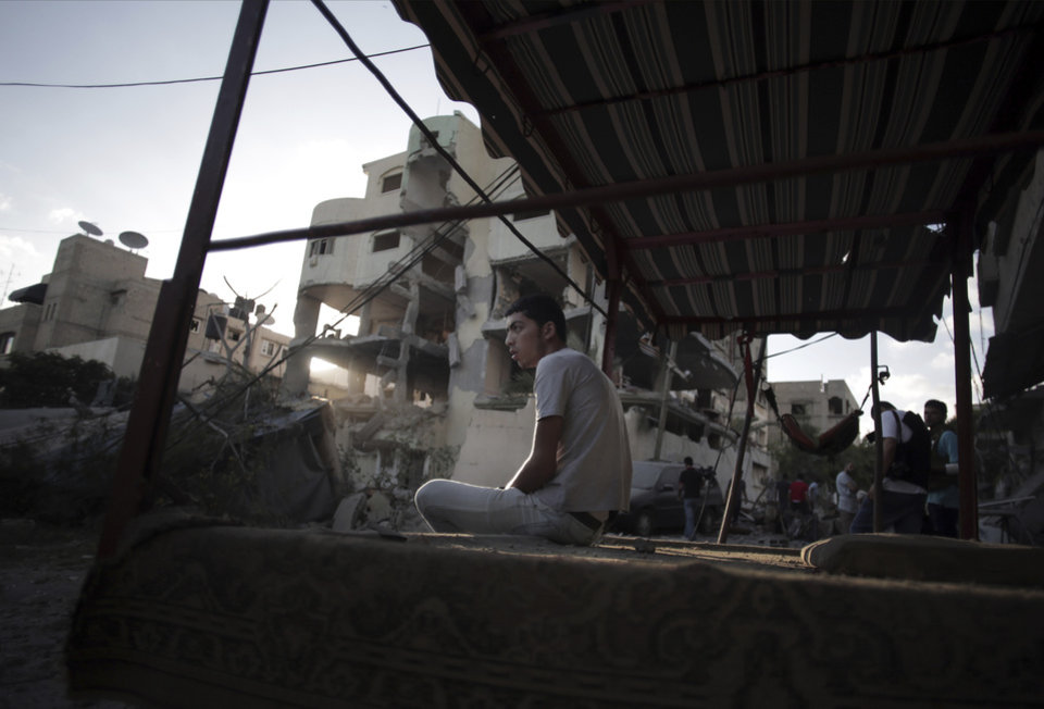 Photo - A Palestinian man sits on a cart next to the house of Hamas leader, Mahmoud Zahar, that was damaged in an early morning Israeli missile strike in Gaza City, Wednesday, July 16, 2014. Israel on Wednesday intensified air attacks on Hamas targets in the Gaza Strip following a failed Egyptian cease-fire effort, targeting the homes of four senior leaders of the Islamic militant movement and ordering tens of thousands of residents to evacuate border areas. (AP Photo/Khalil Hamra)