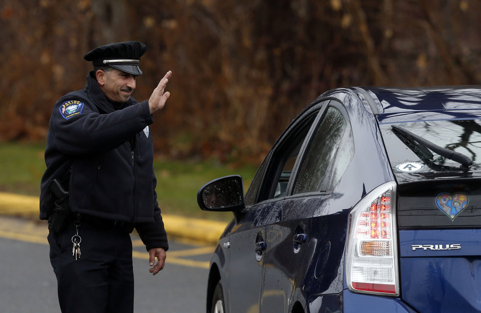 Easton police officer J. Sollazzo waves to a returning student as a car pulls into Hawley School, Tuesday, Dec. 18, 2012, in Newtown, Conn.  Classes resume Tuesday for Newtown schools except those at Sandy Hook. Buses ferrying students to schools were festooned with large green and white ribbons on the front grills, the colors of Sandy Hook. At Newtown High School, students in sweatshirts and jackets, many wearing headphones, betrayed mixed emotions.  Adam Lanza walked into Sandy Hook Elementary School in Newtown,  Friday and opened fire, killing 26 people, including 20 children, before killing himself.(AP Photo/Jason DeCrow) ORG XMIT: CTJD110