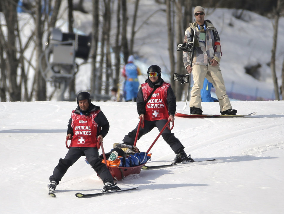 Photo - Jacqueline Hernandez of the United States is carried off the course in a stretcher after crashing in a seeding run during women's snowboard cross competition at the Rosa Khutor Extreme Park, at the 2014 Winter Olympics, Sunday, Feb. 16, 2014, in Krasnaya Polyana, Russia. (AP Photo/Andy Wong)