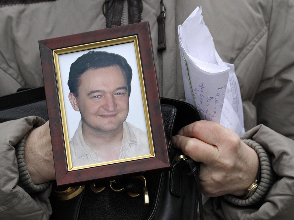 In this Monday, Nov. 30, 2009, file photo a portrait of lawyer Sergei Magnitsky who died in jail, is held  by his mother Nataliya Magnitskaya, as she speaks during an interview with the AP in Moscow. The Senate is taking up legislation Wednesday, Dec. 5, 2012, that would end four-decade-old trade restrictions that are blocking U.S. businesses from enjoying the benefits of a more-open Russian market. The bill also imposes sanctions on Russian human rights violators. The last apparent hurdle to Senate action on the measure came with a decision to accept the House version of human rights legislation that was attached to the trade bill. It is still unclear when a final vote will take place. (AP Photo/Alexander Zemlianichenko, File)