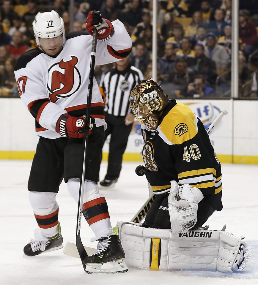 Photo - Boston Bruins goalie Tuukka Rask, right, makes a save as New Jersey Devils' Michael Ryder looks for the rebound during the first period of an NHL hockey game in Boston, Saturday, Oct. 26, 2013. (AP Photo/Winslow Townson)