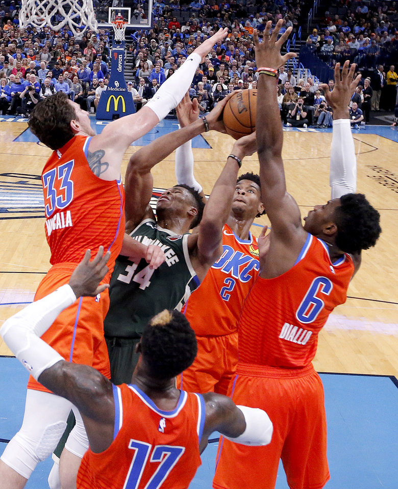 Photo - Oklahoma City's Dennis Schroder (17), Mike Muscala (33), Shai Gilgeous-Alexander (2) and Hamidou Diallo (6) defend against Milwaukee's Giannis Antetokounmpo (34) during the NBA game between the Oklahoma City Thunder and the Milwaukee Bucks at Chesapeake Energy Arena,   Sunday, Nov. 10, 2019.  [Sarah Phipps/The Oklahoman]