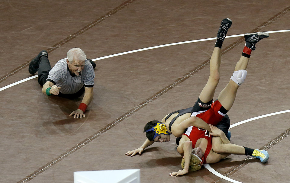 Newkirk\'s Briar Stopp, center, wrestles Locust Grove\'s Braden Bennett in the Class 3A 113-pound Championship match during the state wrestling championships at the State Fair Arena in Oklahoma City, Saturday, Feb. 23, 2013. Photo by Bryan Terry, The Oklahoman