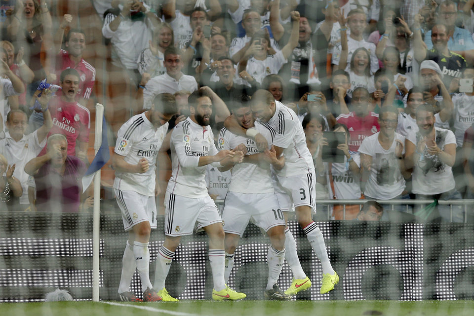 Photo - Real Madrid's James Rodriguez from Colombia, second right, celebrates with teammates after scoring a goal against Atletico Madrid during a Spanish Super Cup soccer match at Santiago Bernabeu stadium in Madrid, Spain, Tuesday, Aug. 19, 2014 . (AP Photo/Daniel Ochoa de Olza)