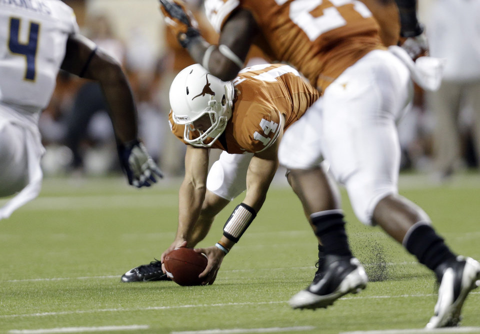 Texas' David Ash (14) chases down a bobbled snap during the fourth quarter of an NCAA college football game against West Virginia, Saturday, Oct. 6, 2012, in Austin, Texas. West Virginia won 48-45. (AP Photo/Eric Gay)