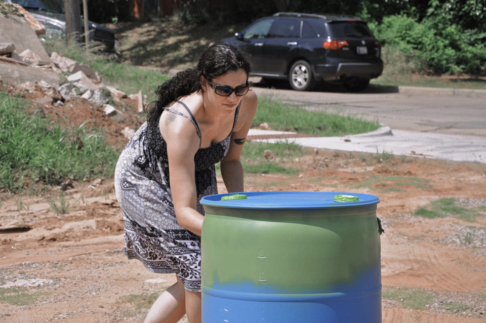 Photo - Gayla Garrett paints her rain barrel during a workshop in the Paseo neighborhood. Another workshop is planned later this month. PHOTO BY M. TIM BLAKE, FOR THE OKLAHOMAN