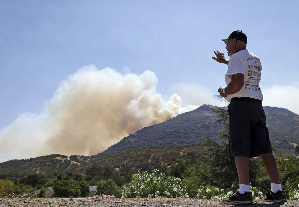 Dave Johnson watches a wildfire burn on Mount Diablo State Park from a view in Clayton, Calif. on Monday, Sept. 9, 2013. A wildfire burning outside Mount Diablo State Park has forced dozens of residents and animals to evacuate Monday. (AP Photo/Marcio Jose Sanchez)